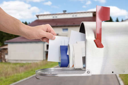 buz�n: Primer plano de la mano del Hombre que toma Carta del buz�n fuera de la casa