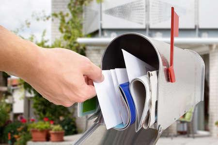 Close-up della mano dell'uomo Prendendo Letter From Mailbox Fuori Casa