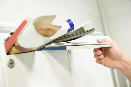 メールボックスから書類を取っている人の手のクローズ アップ 写真素材