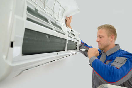 man in air: Portrait Of Young Male Technician Repairing Air Conditioner Stock Photo