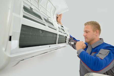 Portrait Of Young Male Technician Repairing Air Conditioner Foto de archivo