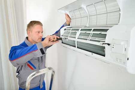 Portrait Of Male Electrician Repairing Air Conditioner Standing On Stepladder