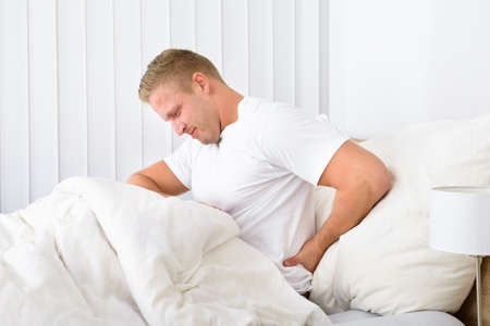 backpain: Portrait Of Young Man Sitting On Bed Suffering From Backpain Stock Photo