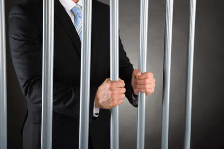 jail: Close-up Of Businessman In Jail Holding Metal Bars