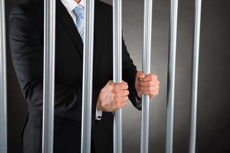 cárcel: Primer plano del hombre de negocios en la c�rcel Bares Holding metal