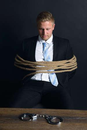 gefesselt: Portrait der jungen Geschäftsmann gebunden mit Seil sitzt vor Tisch mit Handschellen Platziert auf Es