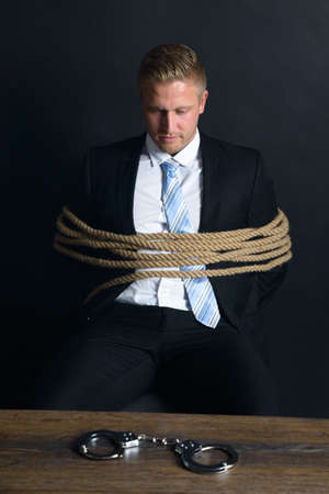Portrait Of Young Businessman Tied With Rope Sitting In Front Of Table With Handcuff Placed On It photo