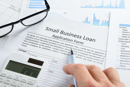 Hand With Pen And Calculator On Business Loan Application Form 스톡 콘텐츠