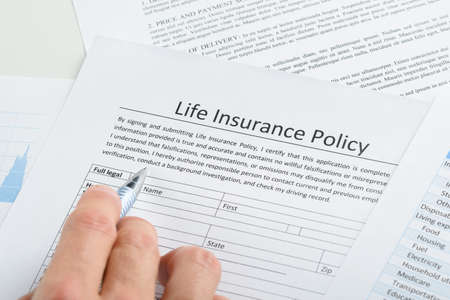생명 보험 정책 신청서를 작성 사람 손의 근접
