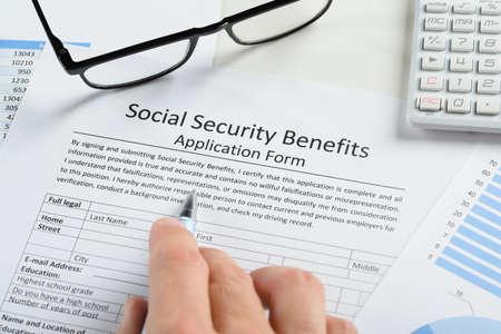Close-up van de hand met pen en brillen Over socialezekerheidsuitkeringen Aanvraagformulier
