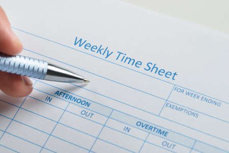 timekeeping: Close-up Of Person Hand With Pen Over Blank Weekly Time Sheet