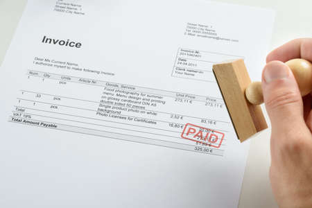 Person Hand Holding Rubber Stamp Over Red Paid Stamp On Invoice Stock fotó
