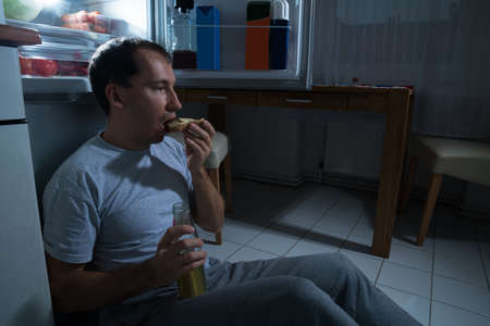 Portrait Of A Man Eating Cheese Bread At Home photo