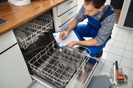 Male Technician Sitting Near Dishwasher Writing On Clipboard In Kitchen photo