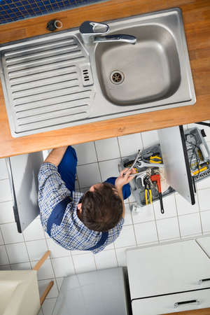 High Angle View Of A Male Plumber Repairing Sink In Kitchen photo
