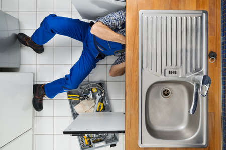 Male Plumber Examining Sink In Kitchen Holding Clipboard photo