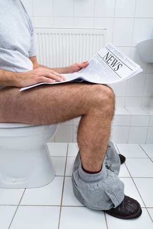 Close-up Of A Man Sitting On Commode Reading Newspaper photo