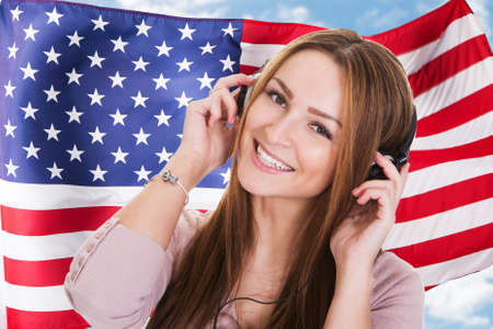 Woman Listening English Language Learning Course Audiobook In Front Of American Flag photo