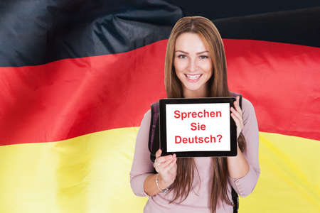 training course: Young Woman Holding Digital Tablet Asking Do You Speak German Stock Photo
