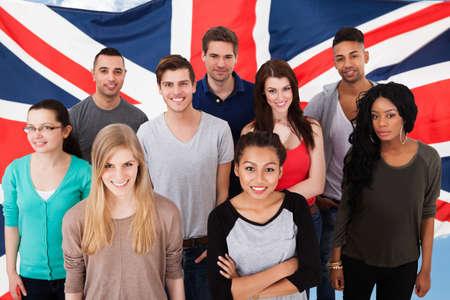 bandera inglesa: Grupo feliz de estudiantes diversa de pie delante de la bandera Uk Foto de archivo