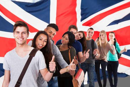 drapeau anglais: Groupe de Happy multi étudiants ethniques debout devant Flag Uk Afficher Thumb Up