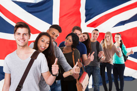 bandera inglesa: Grupo de feliz estudiantes étnicos multi que se coloca delante de la bandera del Reino Unido, mostrando el pulgar