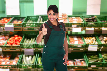 Young Female Sales Clerk Showing Thumb Up Gesture In Supermarket photo