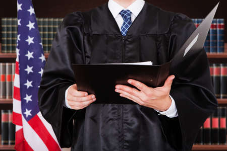 Close-up Of Male Judge Holding Folder In Courtroom
