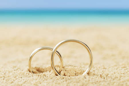 Photos of wedding rings on sand at beach Foto de archivo