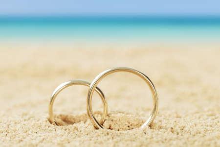 verlobung: Fotos von Trauringen auf Sand am Strand