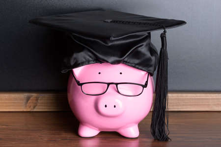 Piggy Bank With Black Graduation Hat And Eye Glasses Near Blackboard