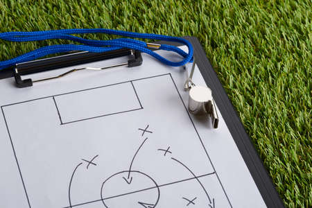 whistles: Whistle And Clipboard With Soccer Tactic Diagram On Green Pitch Stock Photo