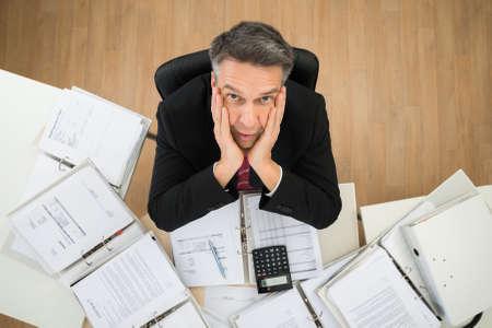 responsabilidad: Preocupado de negocios maduro que mira para arriba con las manos en la mejilla Foto de archivo
