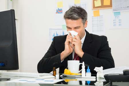 enfermo: Empresario maduro en la oficina turística que sopla su nariz