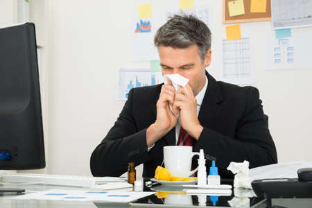 sick person: Mature Businessman At Office Desk Blowing His Nose Stock Photo