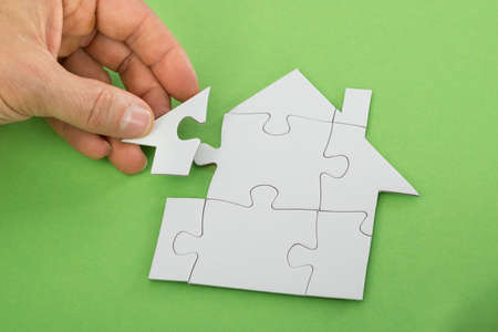 Close-up Of A Persons Hand Solving House Jigsaw Puzzle
