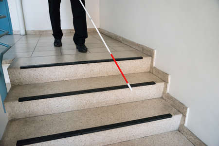 people with disabilities: Blind Man Moving Down On Stairway Holding Stick Stock Photo