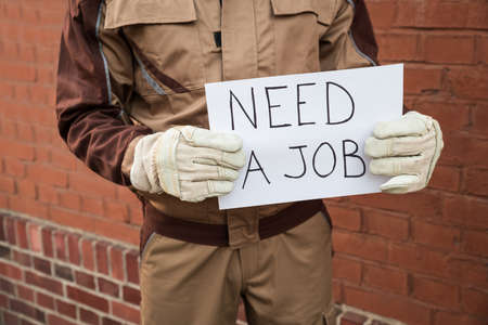 unemployed dismissed: Close-up Of Worker Holding Placard With The Text Need A Job Stock Photo