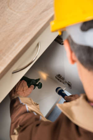 exterminator: Close-up Of Pest Control Worker Spraying Chemicals With Sprayer In Cabinet Stock Photo
