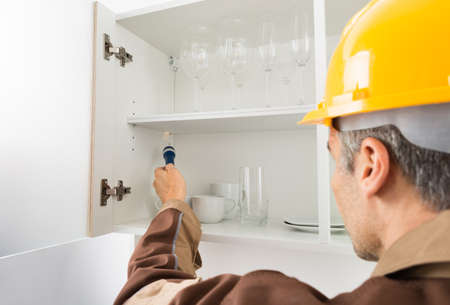 pest control: Pest Control Worker With Flashlight Checking Kitchen Shelf