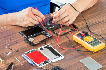 conductor electricity: Close-up Of Hand Repairing Cellphone With Multimeter At The Wooden Table
