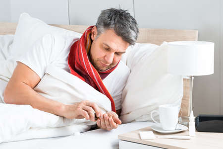 take medicine: Mature Sick Man Lying On Bed Having Medicine