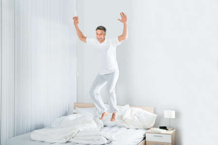 Happy Excited Mature Man Jumping On Bed At Home