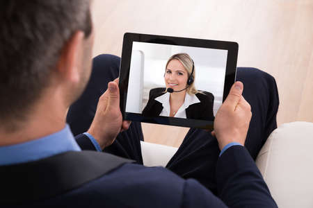 video conference: Businessman Video Conferencing With Businesswoman On Digital Tablet