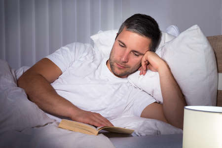 bedsheet: Portrait Of A Man Lying On Bed Reading Book