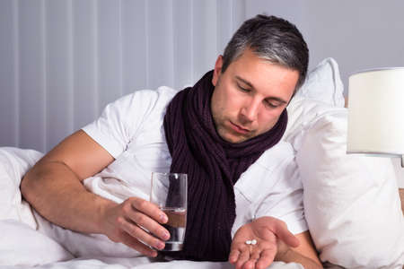 taking medicine: Sick Man On Bed Holding Glass Of Water And Looking At Pills