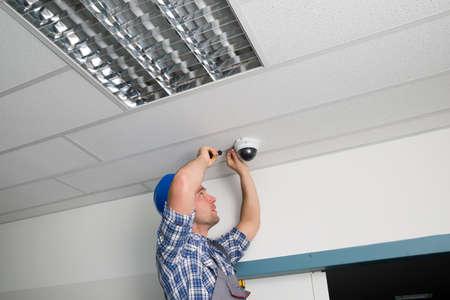 Close-up van mannelijke Technicus aanpassen CCTV camera aan- Plafond Stockfoto