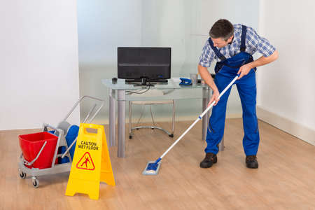 cleaning an office: Portrait Of A Male Janitor Cleaning Office With Wet Floor Sign