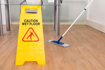 Close-up Of Wet Floor Sign And Mop On Hardwood Floor Stock Photo
