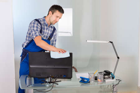 desk tidy: Portrait Of Happy Male Janitor Cleaning Computer On Office Desk Stock Photo
